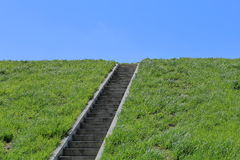 Isolated stairs, green grass, blue sky Stock Photo