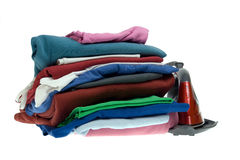 Isolated steam iron and stack shirts Royalty Free Stock Photography