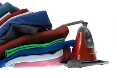 Isolated steam iron and stack shirts Royalty Free Stock Images