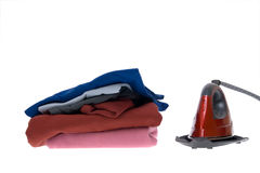 Isolated steam iron and stack shirts Stock Photos
