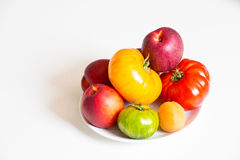 Isolated Still life with tomatoes and fruits. View of a Still life made of on white plate and tomatoes and abricot and Nectarine Royalty Free Stock Photo