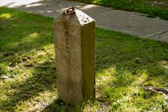 Isolated stone hitching post in Montour Falls. New York near Shequaga Falls. Iron ring on top of post royalty free stock image
