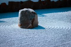 Isolated stone in a raked stone garden. On a spring day at the Japanese gardens in Grand Rapids Michigan stock photo