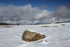 Isolated stone in a snowy landscape in Pyrenees Stock Photos