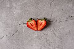 Isolated strawberries. Two heart shaped strawberry fruits cut in half isolated on white background stock images