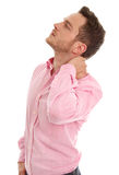 Isolated stressed young business man in pink with neck pain. Stock Photos
