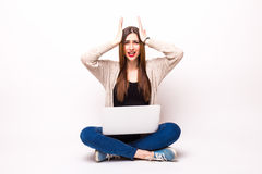 Isolated studio shot of a casually dressed young adult woman staring at her laptop. In surprise Royalty Free Stock Photo