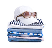 Isolated summer clothes pile with cap and sunglasses on top.  royalty free stock image