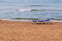 Isolated sunbed on the sandy beach Royalty Free Stock Photo