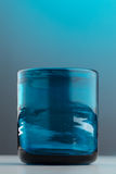 Isolated thick empty blue glass. On a light blue and grey background Royalty Free Stock Photo