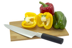 Isolated of three Bell peppers on wooden cutting board with kitchen knife Royalty Free Stock Photography