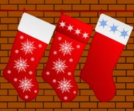 Isolated three red Christmas socks with snowflakes on background. Of brick wall Royalty Free Stock Photos