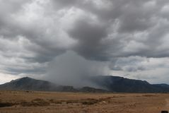 Isolated Thunder Storm in Mountain Pass. An isolated thunder storm showers down on a mountain with gray storm clouds converging, with a brown dirt foreground Royalty Free Stock Photography