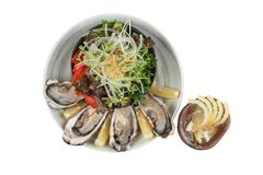 Isolated top view of Fresh oysters and Japanese salad served with Sliced and lemon sauce on white stone bowl.  Stock Photography