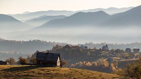Isolated traditional Romanian houses built somewhere in a valley in Transylvania. Romanian traditional houses built on a valley surrounded by mountains, under a stock image
