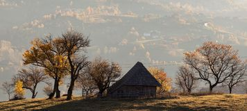 Isolated traditional Romanian houses built somewhere in a valley in Transylvania. Romanian traditional houses built on a valley surrounded by mountains, under a stock photo