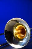 Isolated Trombone Blue Bk. A gold or brass trombone bell isolated against a blue background in the vertical or portrait view Stock Photography
