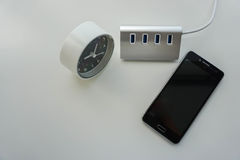 Isolated USB hub for smartphone battery charge with modern clock Stock Photos