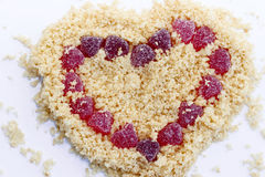 Isolated Valentines Day Heart. Valentines Day Heart background made from yellow biscuits crumbs and red candies Stock Photography