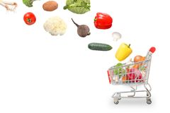 Isolated vegetables fall into the market cart Stock Images