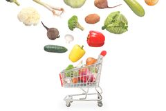Isolated vegetables fall into market cart Royalty Free Stock Image