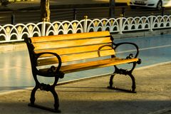 Isolated view of a wooden ironcast street bench under morning sun with a bicycle lane in the background. Street furniture increase quality of life by providing stock image