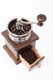 Isolated vintage coffee bean grinder and fresh ground coffee. Next to coffee bean Royalty Free Stock Photo