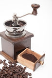 Isolated vintage coffee bean grinder and fresh ground coffee. Next to coffee bean Stock Photos