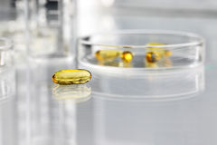 Isolated vitamins pills omega 3 supplements with petri dish. Vitamins pills omega 3 supplements with petri dish on the table Royalty Free Stock Photos