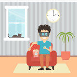 Isolated vr man. Young smiling man using vr glasses sits on armchair with popcorn on white background. Home entertainment. Augmented reality, new technologies Stock Images