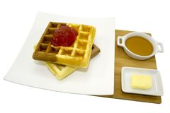 Isolated waffle topped with strawberry jam honey and butter on wooden plate Royalty Free Stock Images