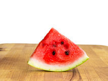 Isolated watermelon slice, cutout quarter on wooden board. Isolated watermelon slice, cutout quarter, fresh red with seeds on wooden board with copyspace Royalty Free Stock Photo