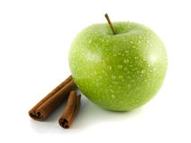 Isolated wet green apple with cinnamon pods Stock Photo
