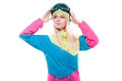 Pretty young woman in ski outfit and ski glasses. Isolated on white, attractive  young caucasian girl in colorful ski suit and blue ski glasses, hands on glasses Stock Photography