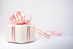 Isolated white box with a bow of pink ribbon. There is isolated white box with a bow of pink ribbon. Gift Royalty Free Stock Images