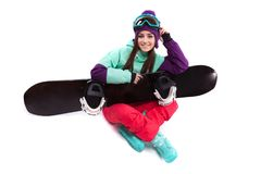 Pretty young woman in purple ski costume siting cross-legged wit Royalty Free Stock Image