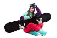 Pretty young woman in purple ski costume siting cross-legged Royalty Free Stock Photo