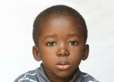 Close-up of African boy being a little sad, angry and full of despair. Isolated on white. Sad little African boy making a facial expression. Here he is being sad Stock Image