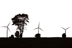 Isolated wind turbine and trees over slope Stock Photo