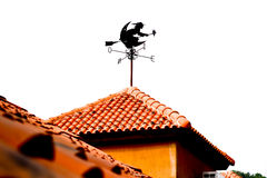 An isolated witch form wind vane  on orange roof. Witch form wind vane and vivid orange roof on white background Stock Images