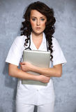 Woman doctor carrying a laptop Royalty Free Stock Image