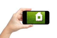 Isolated woman hand holding the phone with house on the screen. Isolated woman hand holding the phone with green grass and a house on the screen Stock Photos