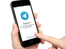 Isolated woman hands holding iPhone with Telegram on the screen Stock Photo