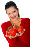 Isolated Woman Offering Tomatoes. Young woman smiling offering fresh tomatoes. shallow depth of field stock photo