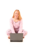 Isolated woman using laptop. In pajamas Stock Image