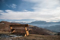 Isolated wooden bench on the edge of the cliff. Towards the mountains covered in snow Royalty Free Stock Photo
