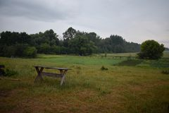 An isolated wooden bench in countryside. Scarecrows, fence, forest, field in the background stock images