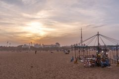 Isolated wooden horse ride swinger for kids during sunset, dark clouds in the background,Marina beach,Chennai,India 19 aug 2017 Royalty Free Stock Photo