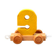 Isolated wooden number nine. Isolated wooden educational toy yellow number nine on the wheels royalty free stock image