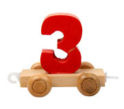 Isolated wooden number three. Isolated wooden educational toy red number three on the wheels Royalty Free Stock Photos